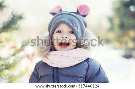Funny baby laughing outdoors in winter day - stock photo