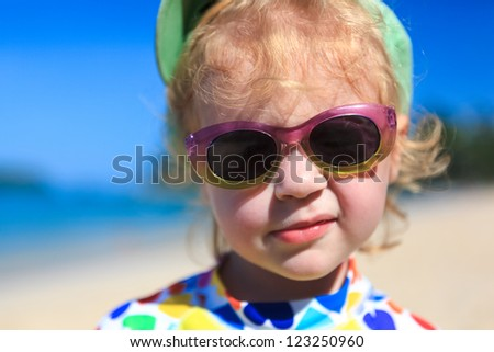 Funny Baby looking at camera on summer beach - stock photo