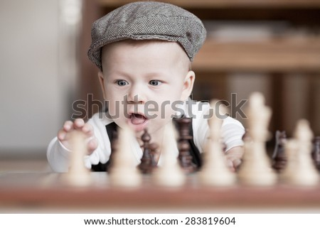 Funny baby playing chess lying on the floor. - stock photo