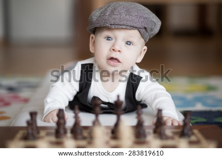 Funny baby playing chess on the floor, looking to the camera. - stock photo