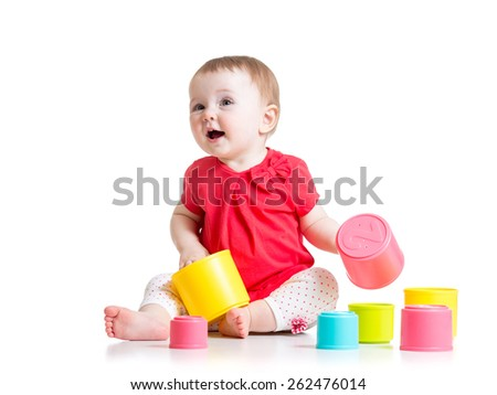 funny baby playing with colourful cup toys on floor, isolated over white - stock photo