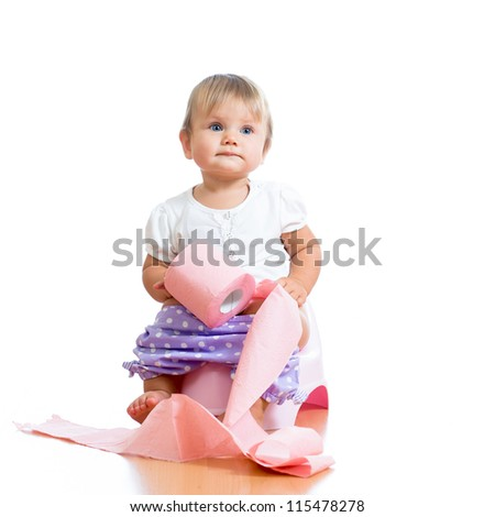 funny baby sitting on chamber pot with toilet paper roll - stock photo