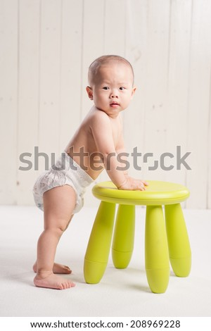 Funny baby standing up against a green chair - stock photo