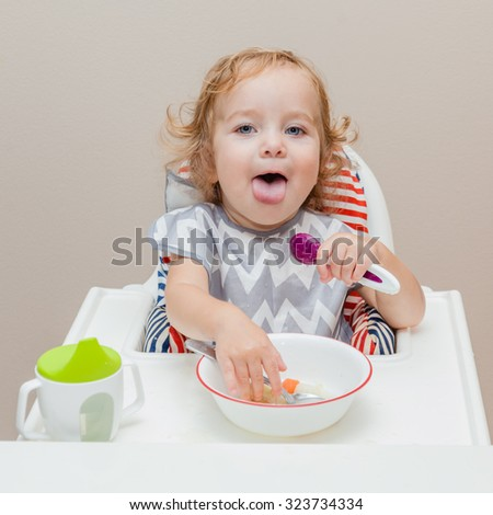 Funny baby stick out his tongue while trying to catch some food in the plate. Child learning to eat himself. Finger food.  - stock photo