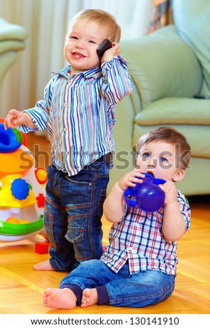 funny baby toddlers playing at home - stock photo