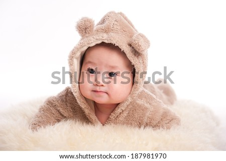 Funny baby wearing a teddy bear suit lying white blanket - stock photo