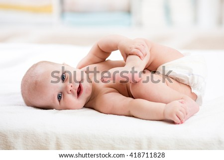 Funny baby wearing diaper. Infant kid skin care. Cute child playing with his feet - stock photo