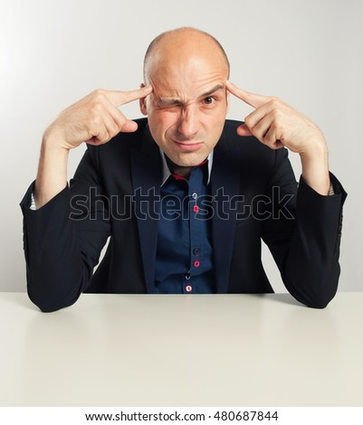 funny bald businessman trying to think seriously. Man Sitting at desk