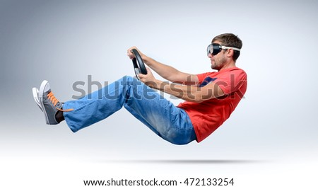 Funny bearded man car driver in goggles with a steering wheel, auto concept