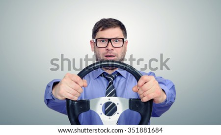 Funny bearded man in glasses with a steering wheel  - stock photo