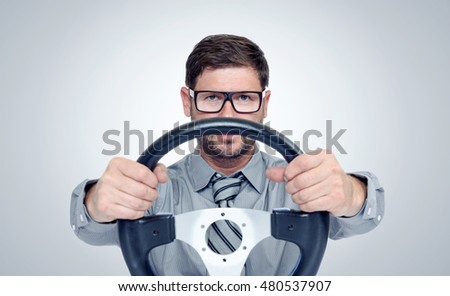 Funny bearded man in glasses with a steering wheel