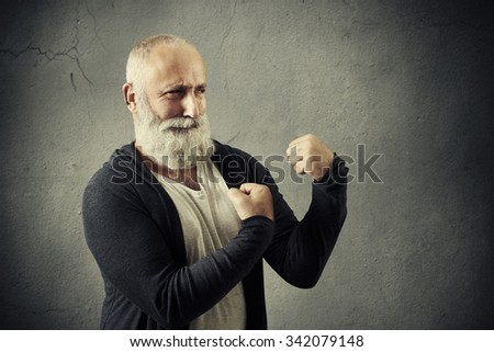 funny bearded man standing in boxing pose over grey wall