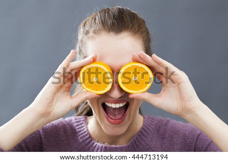 funny beautiful young woman holding two orange slices on her eyes for radiant look or bubbly vitamin c, indoors