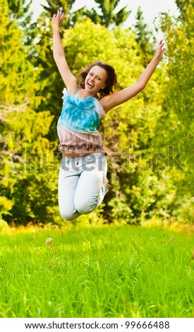 funny, beautiful, young woman jumps up on the background of green grass and forest