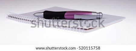 Funny big ballpoint pen on empty notebook against white background