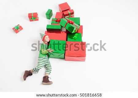 Funny Black Friday, boy dressed in Elf costume holding many gift boxes. Celebrating Christmas. Copy space at white background. Big gift box! Cristmas shopping. Xmas, New Year holiday! Merry Christmas!