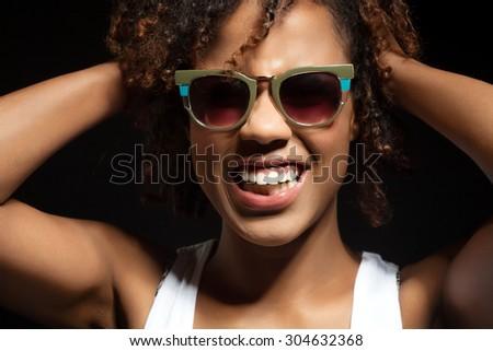 Funny black girl in sunglasses hair whips - stock photo