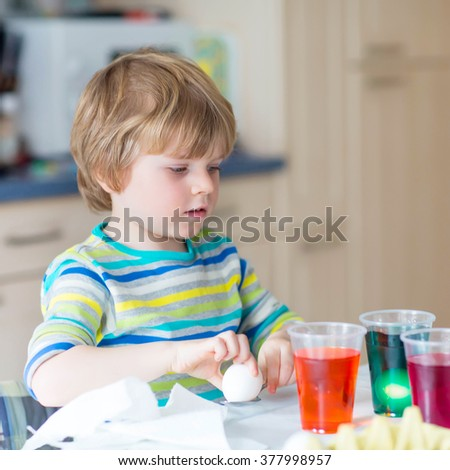 Funny blond kid boy coloring eggs for Easter holiday in domestic kitchen, indoors. Child having fun and celebrating feast.