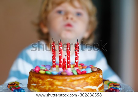 Funny blond kid celebrating his birthday and blowing candles on homemade baked cake, indoor. Birthday party for kids. Focus on cake - stock photo