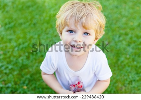 Funny blond toddler boy in summer garden playing with glass of berry ice cubes, creative summer activity with kids. - stock photo