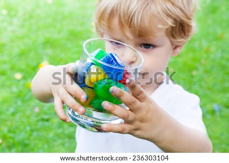 Funny blond toddler boy in summer garden playing with glass of colorful ice cubes, creative summer activity with kids. Selective focus on hands - stock photo
