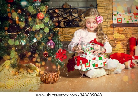 Funny blond toddler girl waiting for surprise from gift present box and making wish ready to celebrate New Year and Christmas at home - stock photo