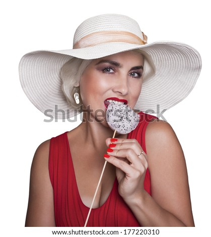Funny blonde in white hat and red dress, eating exotic fruit on a stick. Isolated on a white background. - stock photo