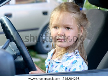 Funny blonde toddler girl sitting of the car on driver seat holding steering wheel  - stock photo