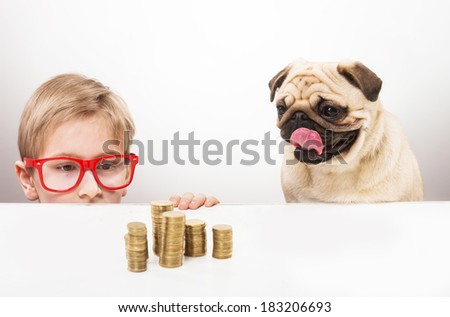 Funny boy and his dog looking over the desk at piles of coins