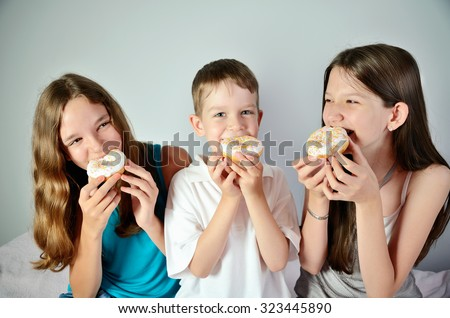 funny boy and two teen girls eating donuts. close-up horizontal - stock photo