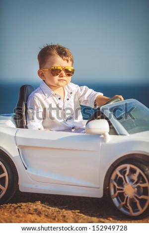 Funny boy car driver with the steering wheel - stock photo