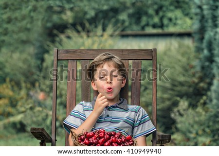 Funny boy eating fresh picked cherry in cherry garden - stock photo