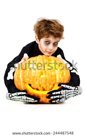 Funny boy in a costume of skeleton holds a pumpkin. Halloween party. Isolated over white. - stock photo