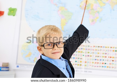 Funny boy in glasses pointing at geographic map - stock photo