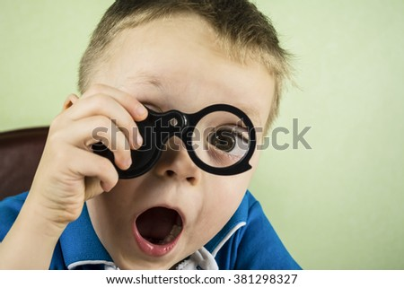 funny boy looking through a magnifying glass eye