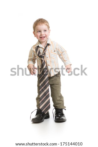 Funny boy playing in big father's shoes isolated on white - stock photo