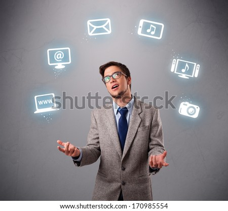 funny boy standing and juggling with electronic devices icons - stock photo