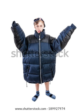 Funny boy wearing a big winter jacket and a cap with a silly expression - stock photo