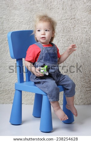 funny boy with a toy in hands sitting in a chair