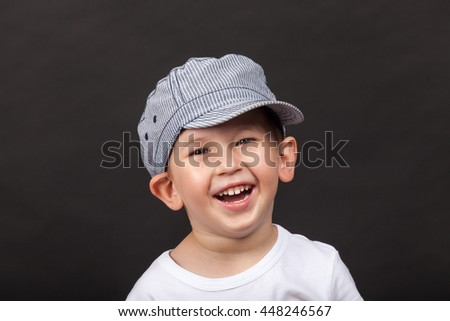 Funny boy with hat laughing.  Studio shot