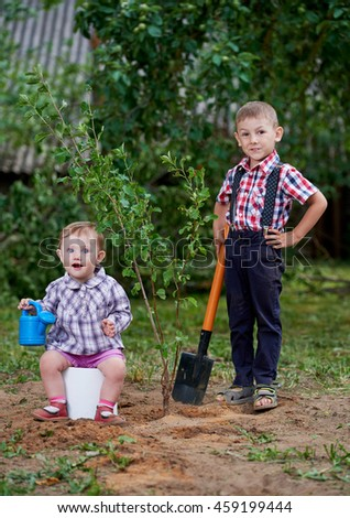 funny boy with shovel in garden