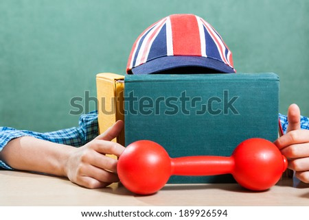 Funny british schoolboy wearing a cap hiding behind books sitting in a classroom over a blackboard  - stock photo
