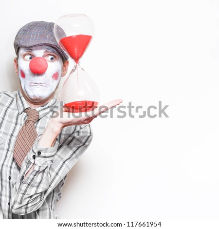 Funny Business Man In Clown Costume Holding An Egg Timer In A Running Out Of Time Concept On Copyspace