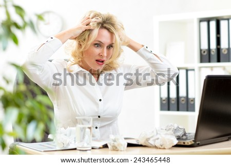 Funny business woman frustrated and stressed holding by head looking at paper heap - stock photo