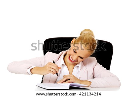 Funny business woman taking notes behind the desk - stock photo
