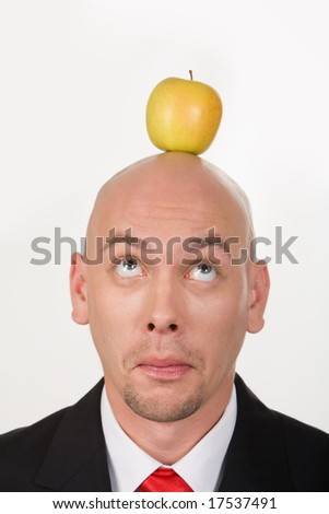 Funny businessman having apple on his head and looking at it - stock photo