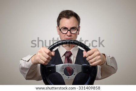 Funny businessman in glasses with a steering wheel, car drive concept - stock photo