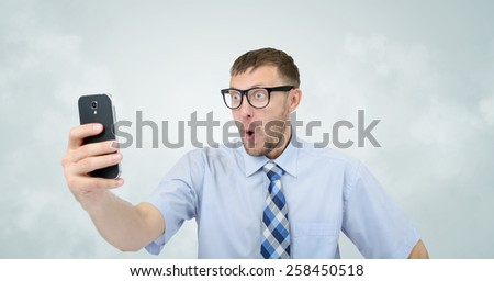 Funny businessman photographing himself on a smartphone. Selfie concept - stock photo