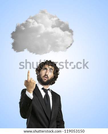 Funny Businessman Pointing Towards Cloud On Blue Background - stock photo