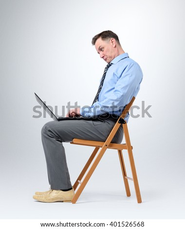 Funny businessman with a laptop sitting in a chair on background - stock photo